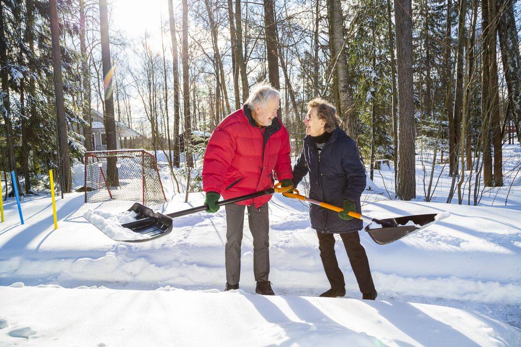Ikääntynyt pariskunta Seppo ja Ainikki lumitöissä keskenään naureskellen.